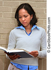 Student Reading - Young female student standing by wall...