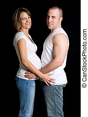 Expecting - expecting couple holding on black background