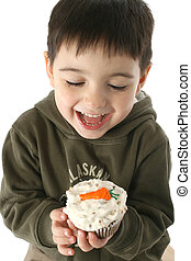 Boy Eating Carrot Cupcake - Close up of happy boy eating...