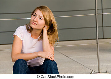sitting girl - Young woman sitting in front of modern...