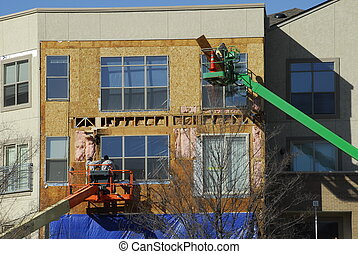 Construction workers working off of manlifts applying siding