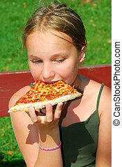 Girl pizza - Young girl eating a slice of cheese pizza...