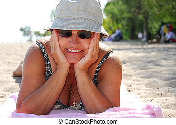 Mature woman beach - Mature woman in sunglasses lying on a...