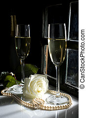 champagne and white rose lit by light through window