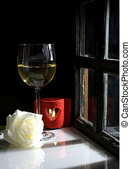 wine - glass of white wine, rose and candle lit by the...