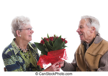 Valentine love - Happy senior couple; the man is giving his...