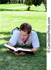 Reading in Grass - Student laying in grass reading book