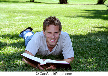 Student in Grass - Student with book laying in grass