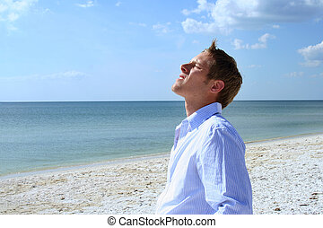 Exhilaration - Man lifting his face to sun on beach