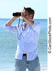 Sight Seeing - Man on beach looking through binoculars