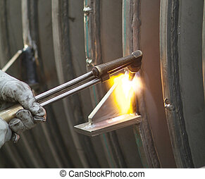 Welder at work - Oxygenacetylene welding flame used on a...