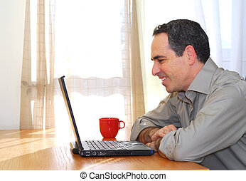 Man with laptop - Man sitting at his desk with a laptop...