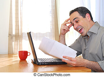Man with laptop - Man sitting at his desk with a laptop and...