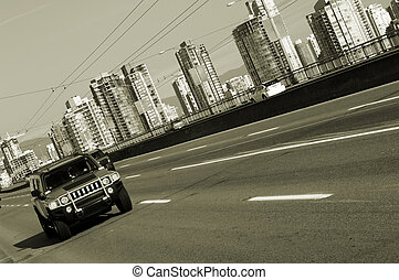 Driving out of town - Sport utility vehicle on the bridge in...