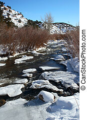 Winter Stream - Partly frozen stream flows through icy...