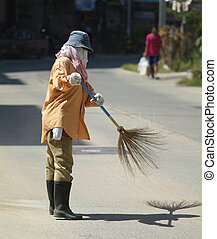 Woman sweeping the street in Pattaya, Chonburi province,...