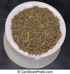 dried dill weed in white dispenser on black background