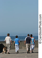 Leisurely Stroll - Four adults out for a stroll on a beach...