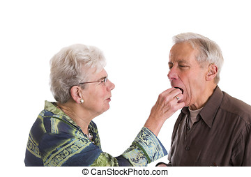 Putting a chocolate in his mouth - Elderly couple having...