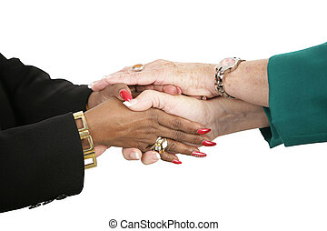 Holding Hands - The hands of two female business people...