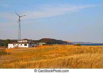 Wind mill and brown grass on lake shore