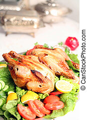 Chicken salad buffet - Two chickens on a bed of salad on a...