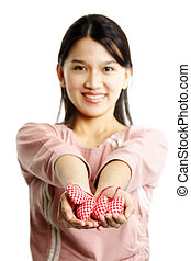 Love - A happy woman showing heart shaped ornaments