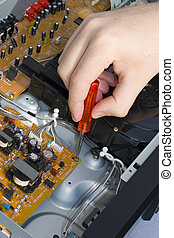 Fix It Up - Hand with Screwdriver on a Circuit Board of Open...