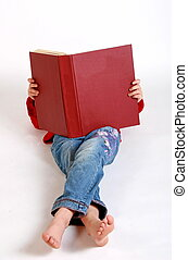 big red book - a young girl lying down reading a huge red...