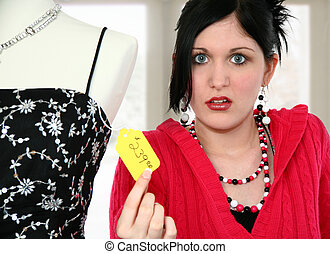 High Prices - Beautiful young woman disgusted with price tag...