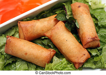 Spring rolls on a bed of lettuce, with a sweet and sour dip