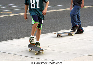 Skateboarders - Two teenage boys on skateboards Shown from...
