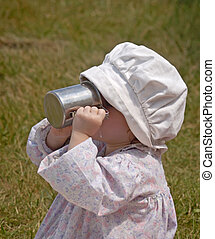 Quenching the Thirst - Little old-fashioned girl drinking...