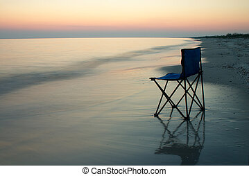 Folding chair on a seaside - Chair standing on a sand on a...