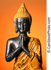 Buddha sculpture at prayer with orange glow background
