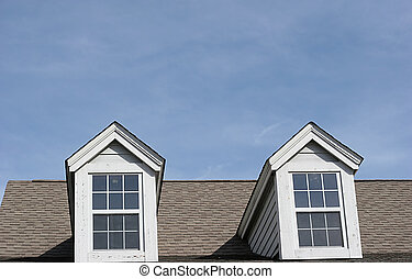 Dormers and roofline of building against blue sky