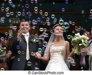 Soap bubbles - Happy newly-married couple on a background of...