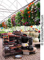 Greenhouse - Flowers and ceramic pots for sale in a...