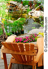 Pond - Natural stone pond and wooden patio chair as...