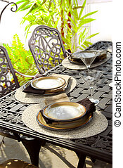 Table setting on a patio table with plates and martini...