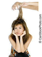 Having Hair Cut - A young attractive asian woman has her...