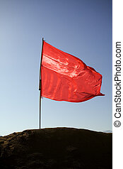 Flag - red flag on a hill against blue sky