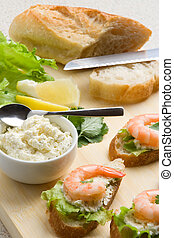 Shrimp toasts with salad, lemon and garlic cheese on a...