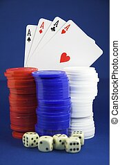 Winning hand - Four aces behind poker chips and dice