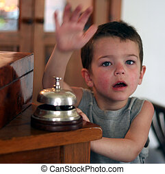 Boy ringing bell - a boy is ringing a bell in a hotel lobby
