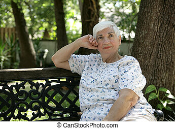 Daydreaming in the Park - A sweet senior lady daydreaming in...