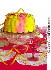 Birthday Cake - A pink and yellow iced birthday cake on a...