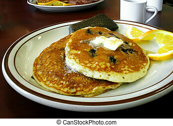 Pancakes - A plate of blueberry pancakes with a slice of...