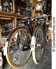 Two old bicycles in a room full of old junk
