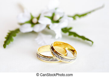 Wedding rings with small flower on white background